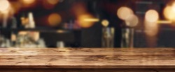 Night panorama with bokeh in a bar in front of an empty wooden table for a solemn concept