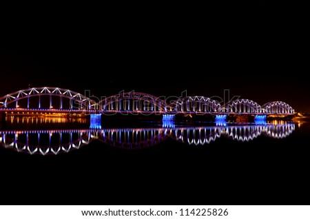 night panoramic scene with railway bridge in Riga, Latvia