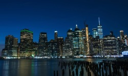 Night photo of glowing skyscrapers and a view of Manhattan Bay. Long duration. Panoramic photo. The splendor of the city at night.