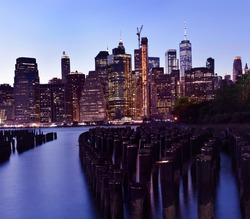 Night photo of glowing skyscrapers and a view of Manhattan Bay. Long duration. Vertical panorama. The splendor of the city at night.