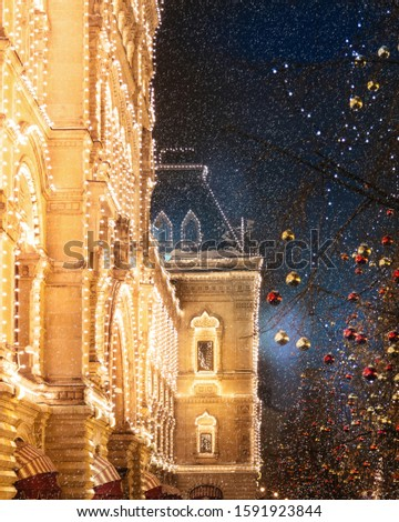 Night photo of illumination and decoration of GUM shop and red square during a snowfall. Red and golden Balls decorate trees, thousands of light bulbs illuminate the building. Christmas celebration.