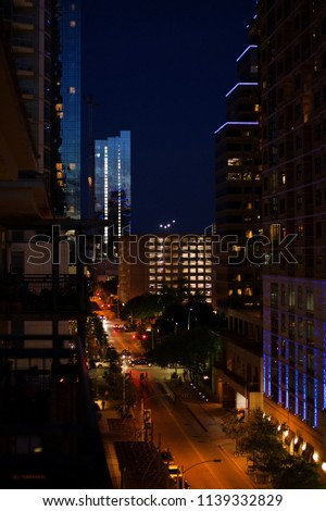 Night photo of 2nd Street downtown Austin, TX in twilight.  Twilight sky is reflected in building windows while street lights and car lights illuminate the street and pedestrian traffic. #1139332829