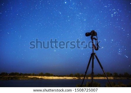 Night photography. Silhouette of camera on tripod on background of starry sky. Long exposure. Many stars in night blue sky. Dark starry landscape. Shooting equipment. Take picture. Professional camera