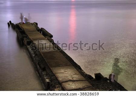 night pier with fisherman's shadows taken on long exposure