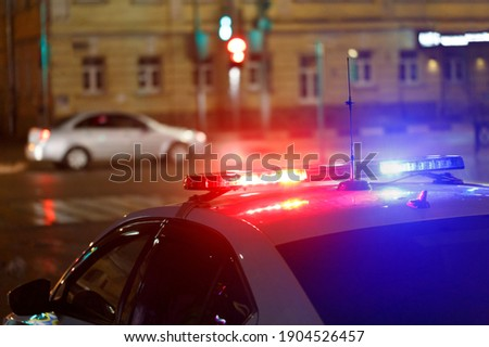 night police car lights in city street with civilian car in blurry background ストックフォト ©
