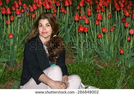 Night Portrait in tulip garden: Beautiful Hispanic woman sitting on the grass with flowering tulips
