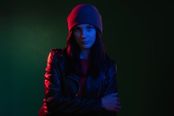 Night portrait. Neon light. Female power. Gender equality. Rebellious woman in hat leather biker jacket standing in red blue glow isolated on dark green copy space background.