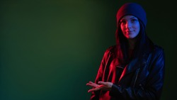 Night portrait. Neon light. Street style woman. Information banner. Confident lady in hat leather biker jacket in red blue glow showing copy space isolated on dark green advertising background.