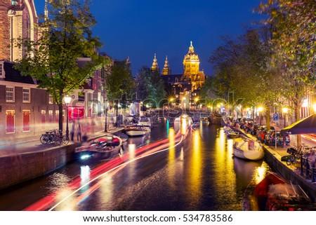 Night red-light district De Wallen, canal, Basilica of Saint Nicholas and bridge, Amsterdam, Holland, Netherlands. Long exposure. Used toning