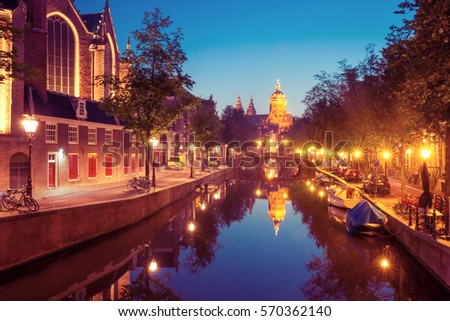 Night red-light district De Wallen, canal Oudezijds Voorburgwal, bridge, Basilica of Saint Nicholas and its mirror reflection, Amsterdam, Holland, Netherlands. Long exposure.