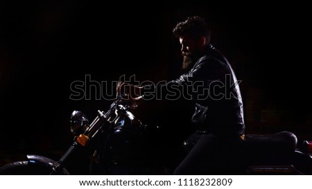 Night rider concept. Man with beard, biker in leather jacket sitting on motor bike in darkness, black background. Hipster, brutal biker in leather jacket riding motorcycle at night time, copy space. #1118232809