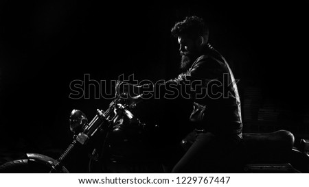 Night rider concept. Man with beard, biker in leather jacket sitting on motor bike in darkness, black background. Hipster, brutal biker in leather jacket riding motorcycle at night time, copy space. #1229767447