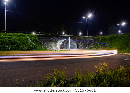 Night road with tracer by car, lit lamps.