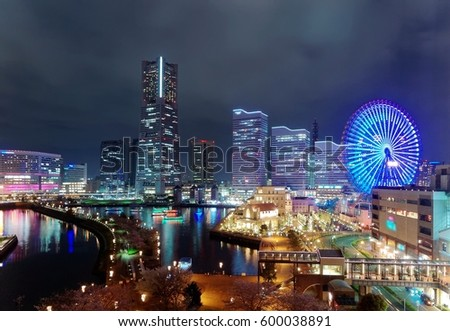 Night scape of Minatomirai Bay Area in Yokohama, Japan, with Landmark Tower amid high rise buildings in background, a giant Ferris wheel in an Amusement Park & sightseeing boats cruising in the harbor #600038891