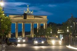 night scene Brandenburg Gate lit with car pedestrian traffic at night on Unter den Linden Berlin Germany Europe