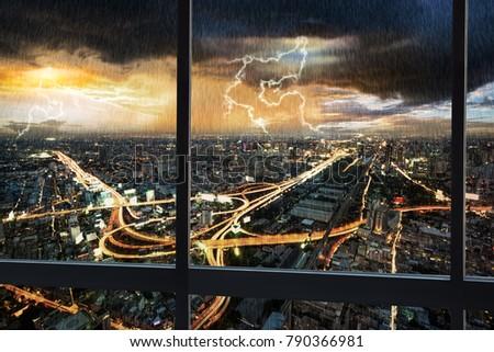 Night scene cityscape traffic with rain storm and thunderbolt lightning shoot from window internal building in Bangkok metropolis Thailand #790366981