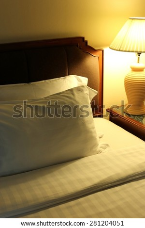 Night scene image of comfortable pillows and bed, Hotel room Interior.
