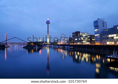 Night scene in Duesseldorf at the Rhine river with the Rheinturm Tower, toned image.