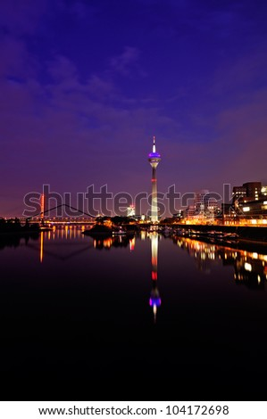 Night scene in Dusseldorf at the Rhine river with the Rheinturm Tower, toned image.