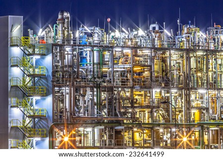 Night scene of detail of a heavy Chemical Industrial plant with mazework of pipes in twilight