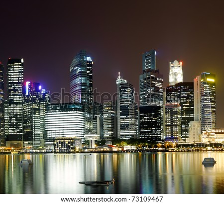 Night scene of modern city with buildings and river in Singapore, Asia.
