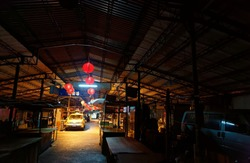 Night scene of Muo-Fun Market, a traditional Taiwanese marketplace in Taichung, with a taxi parking in the alley between closed stalls & red lanterns hanging down from the ceiling in a nostalgic mood