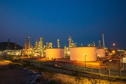 Night scene of oil refinery plant and storage white tank oil of Petrochemistry industry in twilight time