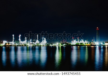 Night scene of oil refinery plant of Petrochemistry industry in twilight time and reflection in near river, gas and oil production processing in Bangkok, Thailand. stock photo