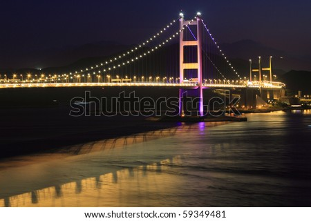 night scene of Tsing Ma bridge and reflection in Hong Kong, key infrastructure leading to the international airport