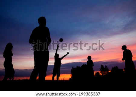 Night scene. Silhouettes of young people playing with a ball on the sunset sky background