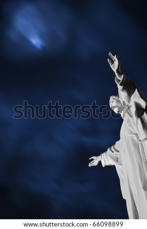 Night scene with a statue of Jesus Christ in the forefront - stock photo