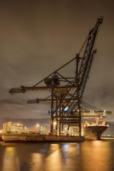 Night scene with illuminated container terminal, massive crane and moored vessel, Port of Antwerp, Belgium.