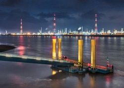 Night scene with illuminated mooring pier in river and illuminated refinery on riverbank, Port of Antwerp