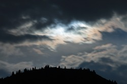 Night scenery of clouds, illuminated by the moon with the silhouette of trees and mountains, Almaty.