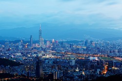 Night scenery of Downtown Taipei, the vibrant capital city of Taiwan, with view of Taipei 101 Tower among high-rise buildings in Xinyi Financial District & bridges over Keelung River in blue twilight