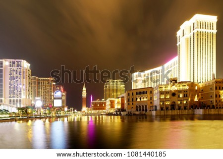 Night scenery of the grand exterior of The Venetian Macao among buildings of luxury hotels & extravagant casino resorts in Macau, China, with beautiful reflections of colorful neon lights in the water #1081440185