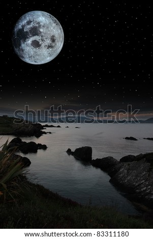 night scenic view in kerry ireland of rocks and sea with mountains against a beautiful blue cloudy sky