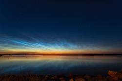 Night shining clouds (noctilucent clouds) over lake in Sweden, with kinnekulle in the background