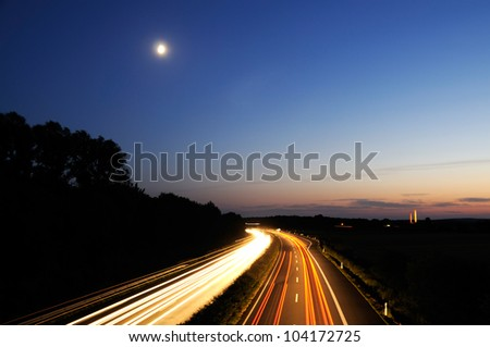 Night shot (long exposure) of curve on german autobahn and motion blured car lights - stock photo