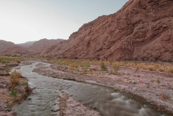 Night shot. Magical landscape at sunset. Beautiful view of the pure water stream flowing across the desert, canyon and red sandstone mountains with dusk colors.