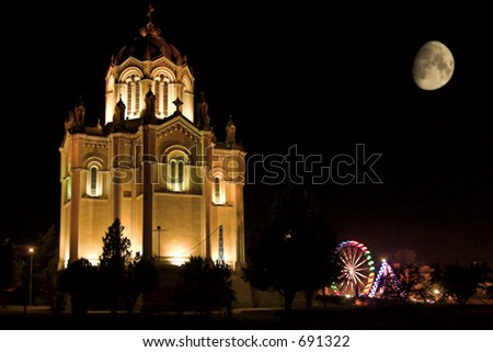 Night shot of a fair with a big moon, a pantheon and a big wheel.