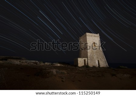 Night shot of a fortification tower in Malta with star trails behind it.
