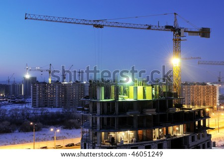 night shot of construction building site with tower crane loader
