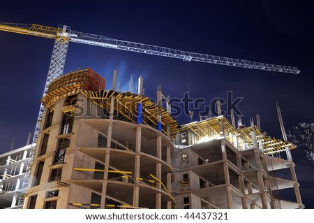night shot of construction equipment at building site