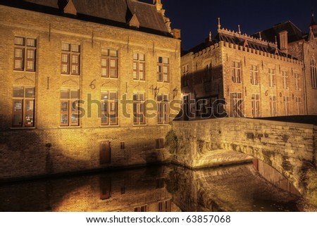 Night shot of historic medieval buildings along a canal in Bruges, Belgium, which is on the world heritage list of unesco
