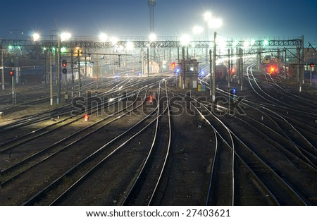 Night shot of railway station tracks curving and going to the horizon