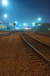 Night shot of railway station with curving track and bridge over railroads and passing train trail in the background
