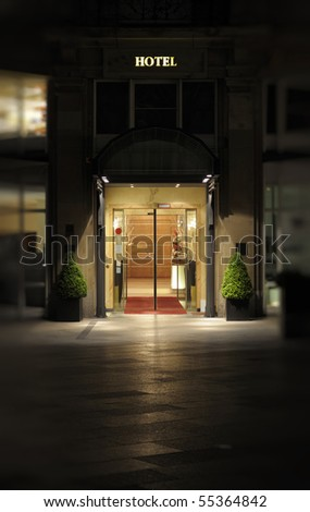 Night shot of the entrance and facade to a luxury hotel.