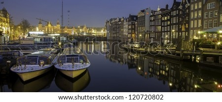 Night shot of Traditional houses and boats in Amsterdam, capital of Holland, Netherlands,  with reflections in the canal