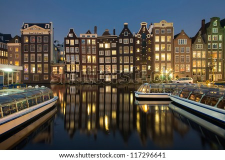 Night shot of Traditional houses in Amsterdam, capital of Holland, Netherlands,  with reflections in the canal